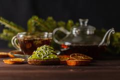 Transparent glassy tea cup with tea on the black background Stock Photos