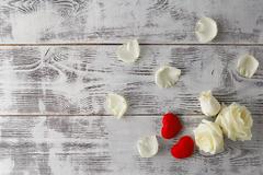 Valentine background, white rose flowers and petals scattered on white rust.. Stock Photos