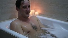 A young man sitting pretty in the bathroom with foam and making thumbs up, slow Stock Footage