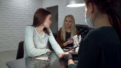 Brunette and blonde girls receive a manicure in the salon for nail art Stock Footage