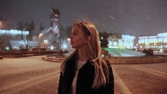 A young girl in a winter evening in the town square. The lights of the houses Stock Footage
