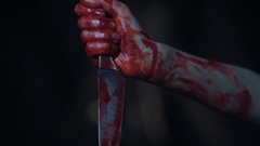 Fanatic's hands covered with blood holding murder weapon, human sacrifice, fear Stock Footage