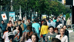 Crowd of People Walking on City Street on Summer Background of Trees And Stock Footage