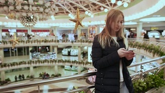 Cute young girl in jacket, making a call, talking on a cell phone in a large Stock Footage