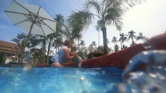 Elderly woman plays with little girl in pool Stock Footage