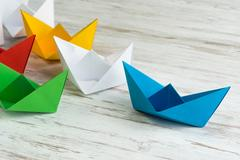 Business leadership concept with white and color paper boats on wooden table Stock Photos