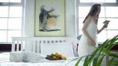Woman sitting down on bed with postcard Stock Footage
