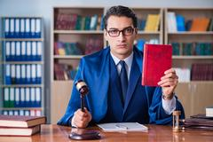 Handsome judge with gavel sitting in courtroom Stock Photos