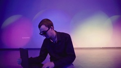 Man using a laptop being alone on the dance floor Stock Footage