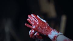 Syringe with blood in hands of crazy serial killer, horrible bloody scene Stock Footage