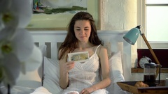 Woman sitting in bed with postcard Stock Footage