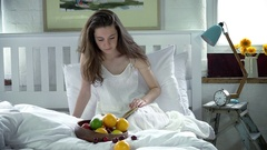 Woman reading and eating in bed Stock Footage