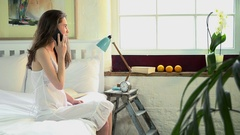 Woman sitting on bed talking on phone Stock Footage