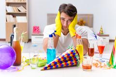 Man cleaning the house after christmas party Stock Photos