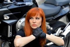 Serious,powerful,thinking leader of bikers sit near the bike and look aside Stock Photos