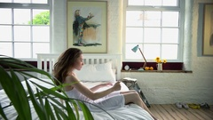 Woman standing up from bed with phone Stock Footage