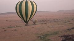 AERIAL: Safari hot air ballon descending toward scorched savanna grassland field Stock Footage
