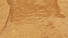 Rapid flowing water stream in fine sand bed carrying sand along, creating Stock Footage