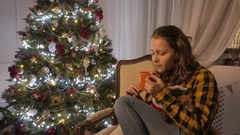 Teen girl smiling and drinking tea from a cup. Christmas tree and holidays mood Stock Footage