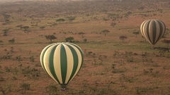 AERIAL: Two safari hot air balloons floating above endless Serengeti plains Stock Footage