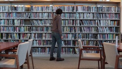 Man Using local Library Searching for Books Stock Footage