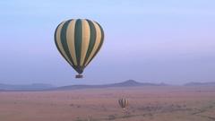 AERIAL: Safari hot air ballon descending landing on savanna grassland field Stock Footage