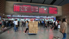Passengers walk and buy tickets inside of a train rail station in Beijing, China Stock Footage