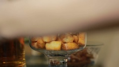 Fresh chilled glass of beer with snack crackers. man's hand takes croutons Stock Footage