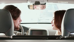 Couple turns their faces to the back seat inside the car Arkistovideo