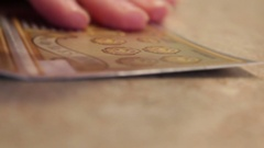Hand scratches out scratch off lottery ticket with coin Stock Footage
