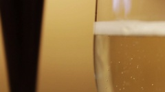 Close up of Glass of Champagne bubbling near lamp in ambient setting Stock Footage