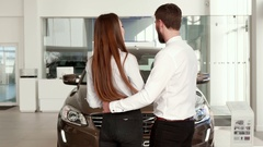 Couple comes closer to the black car at the dealership Stock Footage