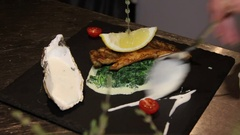 Decoration of fish with spinach and capers sauce Stock Footage