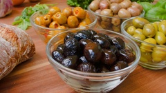 Several kinds of olives in glass bowls Stock Footage