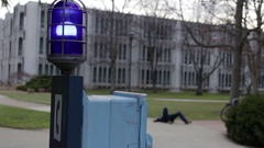 Injured college student on ground yards away from emergency call box Stock Footage