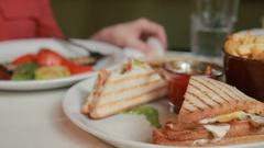 Female hands holding otkusanny sandwich on a plate. Restaurant Stock Footage
