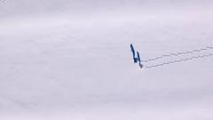 Aerial - Extreme long shot of two people walking through powder snow Stock Footage