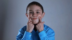 Little boy grimacing and having fun. White background Stock Footage