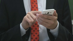 Man holding a smartphone indoors Stock Footage