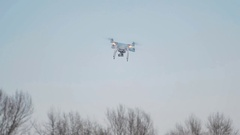 Drone quadcopter hovered in the blue sky Stock Footage
