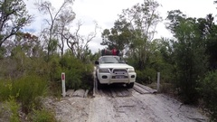 4x4 vehicle driving over old wooden bridge on Fraser Island Stock Footage