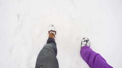 Legs Man and woman in winter boots walking in the snow next to each other Stock Footage