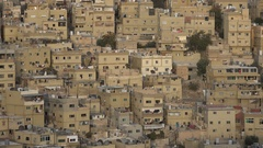 Pigeons fly over homes in a residential area in Amman Stock Footage