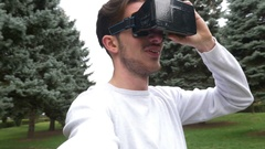Man wearing virtual reality goggles in park moving and interacting with the.. Stock Footage
