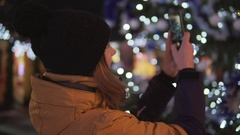 Young woman in bright winter clothes taking photo with mobile phone at the Stock Footage