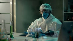 Scientist man in respirator putting on protective gloves before performing an Stock Footage