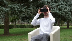 Young man looking around in a virtual reality world using VR glasses and le.. Stock Footage