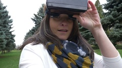 Woman putting vr headset on and looking around outdoor in a virtual world Stock Footage