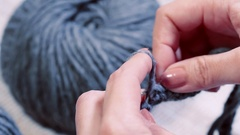 Close-up of hands knitting with spokes of natural wool winter hat gray. Stock Footage