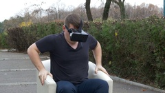 Scared man using VR goggles and watching 3d multimedia content while sittin.. Stock Footage